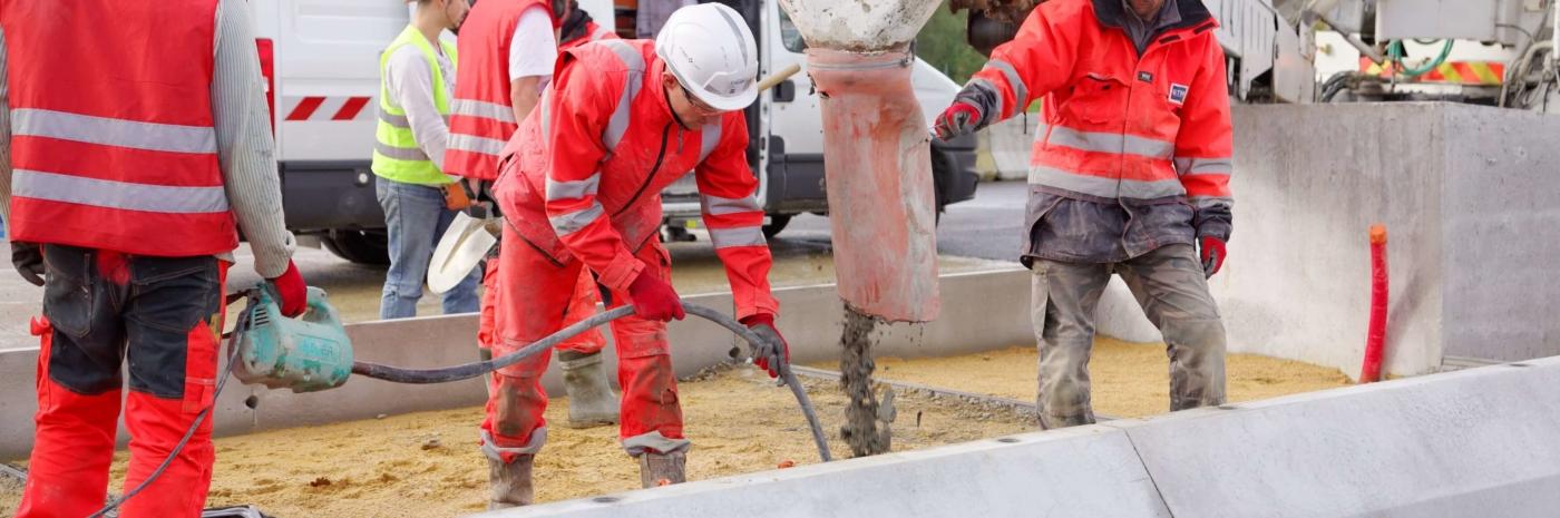 collaborateurs GTM TS coulant du béton dans un îlot de péage